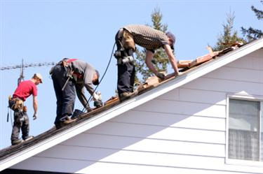 Roof Installation in Manor TX. Three roofers laying new shingle on a roof in Manor.